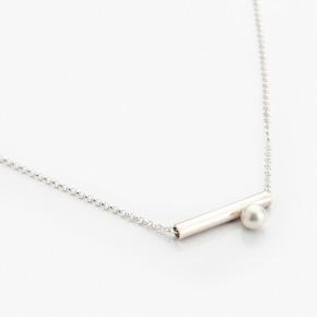 Elegantní přívěšek na krk ozdobený perličkou.